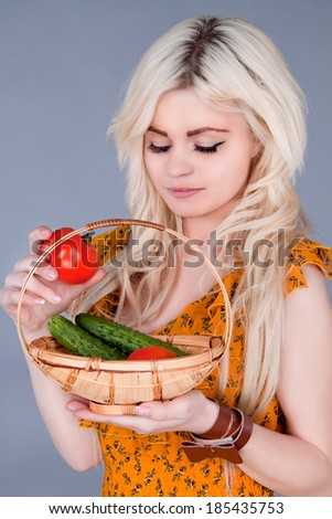 blonde girl lays down a basket of tomatoes and looking down