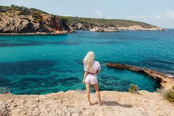 Blonde girl looking at Cala Portinatx from the coast in Ibiza, Spain. Beautiful woman looking to the blue aqua sea. Back view.
