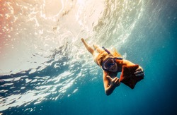 Blonde girl making diving in a clear blue sea with mask and holding in hands a orange starfish. Young woman showing thumbs up during swimming in a tropical place. Concept of wanderlust and adventure
