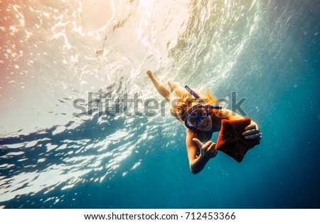 Blonde girl making diving in a clear blue sea with mask and holding in hands a orange starfish. Young woman showing thumbs up during swimming in a tropical place. Concept of wanderlust and adventure #712453366