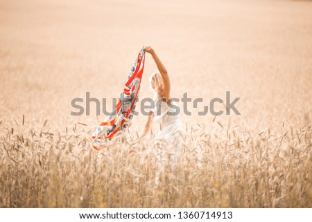 Blonde girl model on a wheat field. Young woman enjoying nature. Beautiful girl raising her hands in the rays of sunlight. Sunlight. #1360714913