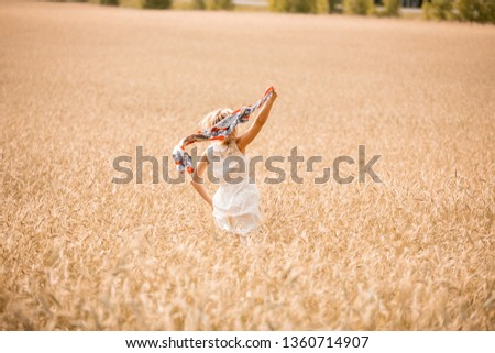 Blonde girl model on a wheat field. Young woman enjoying nature. Beautiful girl running in the rays of sunlight. Sunlight. #1360714907