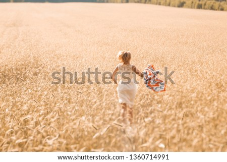 Blonde girl model on a wheat field. Young woman enjoying nature. Beautiful girl running in the rays of sunlight. Sunlight. #1360714991