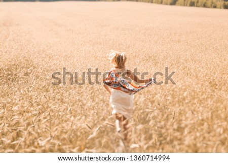 Blonde girl model on a wheat field. Young woman enjoying nature. Beautiful girl running in the rays of sunlight. Sunlight. #1360714994