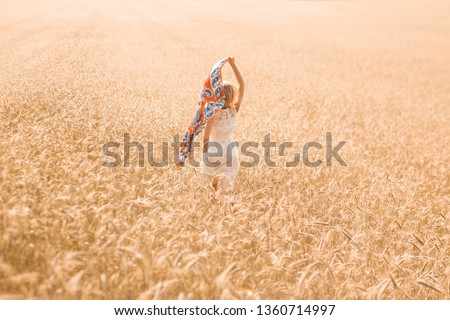 Blonde girl model on a wheat field. Young woman enjoying nature. Beautiful girl running in the rays of sunlight. Sunlight. #1360714997