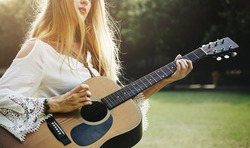 Blonde Girl Playing Guitar In The Park Concept