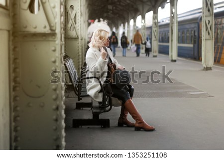 Blonde girl sitting on a bench on the train platform and straightens her hair. In the distance there are other passengers.