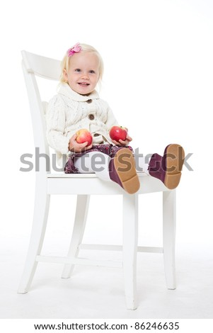 Blonde girl sitting on a chair with two red apples