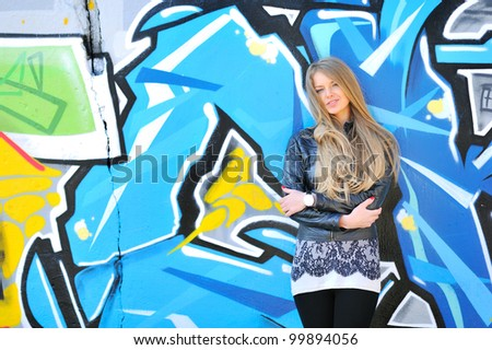 Blonde girl smiling against grafitti wall - stock photo