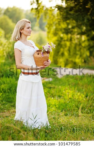 Blonde girl staying in the park and holding vase with flowers, looking forward, daylight
