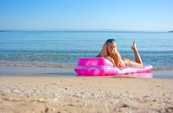 Blonde girl swimming on mattress in the sea