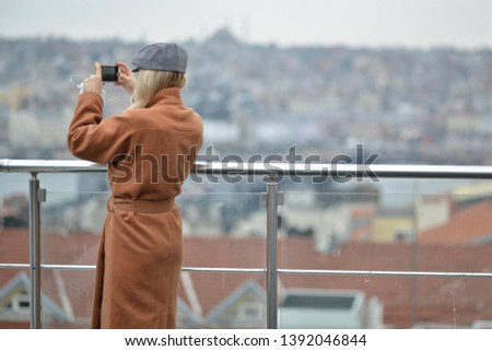 blonde girl taking picture of landscape