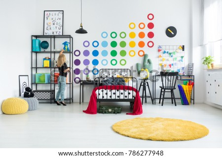 Stock Photo Blonde girl tidying her colorful room with dot stickers on the white wall and round yellow rug