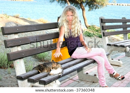 Blonde girl touching cat on the bench.