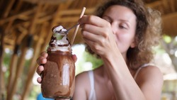 Blonde girl tries whipped cream of chocolate milkshake and enjoys it with closed eyes. Dessert in a beach cafe