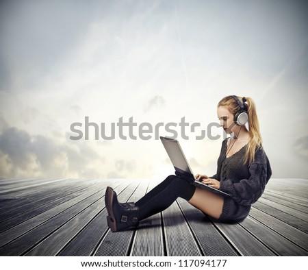 Blonde girl using a laptop computer outdoor