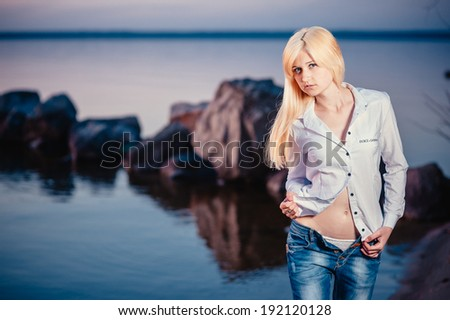 Blonde girl walking barefoot in jeans and a white shirt on the river at sunset. Walk on the water after work