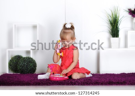 Blonde girl, wearing a dress, talking on the toy phone, calling mom