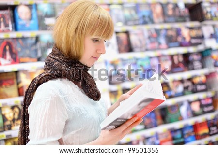 Blonde girl wearing scarf reads book in supermarket; shallow depth of field