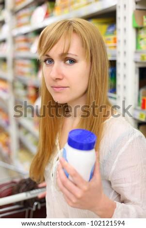 Blonde girl wearing white shirt keeps salt in store; shallow depth of field