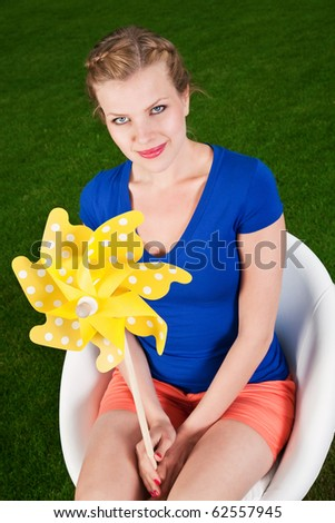 blonde girl with a pinwheel on a swivel chair
