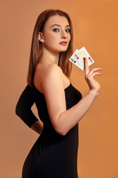 Blonde girl with bright make-up, in black dress is showing two aces, posing sideways against colorful background. Gambling, poker, casino. Close-up.