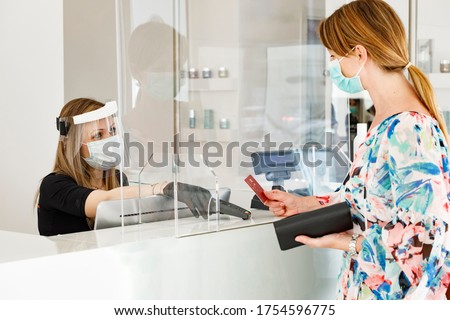 blonde girl with mask pays at the checkout with a credit card where the cashier is protected by a plexiglass plate and a visor with mask