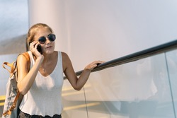 Blonde girl with sunglasses and a bag hanging from her shoulder talking on her mobile phone as she climbs the escalator in a modern building in Singapore
