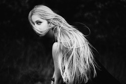 Blonde girl with very long hair on dark fone.Zhensky portrait. Conceptual photography. The girl's face is covered with hair.