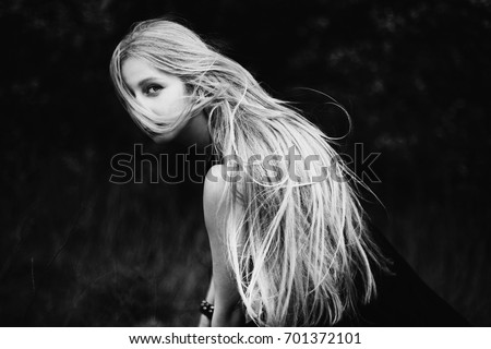 Stock Photo Blonde girl with very long hair on dark fone.Zhensky portrait. Conceptual photography. The girl's face is covered with hair.