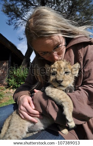 Blonde girl with young lion cub