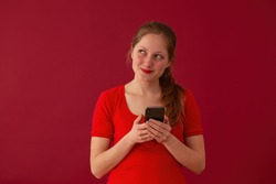Blonde girl wondering about message on valentines day. Woman with phone thinking on red background..Female with lipstick smiling and holding smartphone.