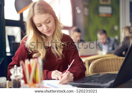 Blonde girl writing in notebook