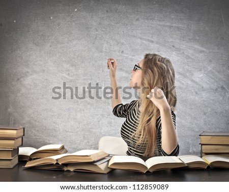 Blonde girl writing on a black blackboard - stock photo