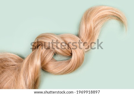 Blonde hair lock tied in knot. Strand of honey blonde hair on mint background, top view. Hairdresser service, hair strength, haircut, hairstyle, dying or coloring, hair extension, treatment concept