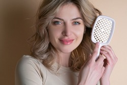 Blonde hair. Perfect woman with with a comb. Beautiful woman with curly hair. Care. Female model after hair procedure. Natural health glance hair on beige background