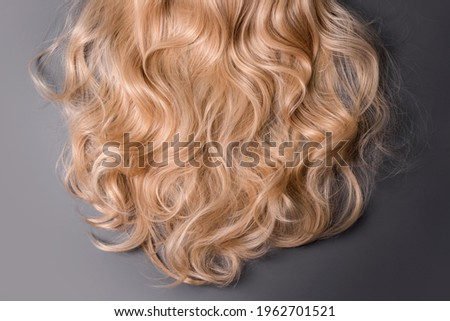 Blonde hair texture. Wavy long curly blond hair close up as background. Hair extensions, materials and cosmetics, wig, hair care. Hairstyle, haircut or dying in salon Foto d'archivio ©