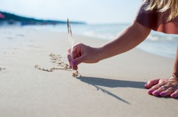 Blonde hair young woman is writting with a bird feather on sand. Girl drawing a heart on the sand at sunset in a summer love concept. A girl writing with sands with the sea background