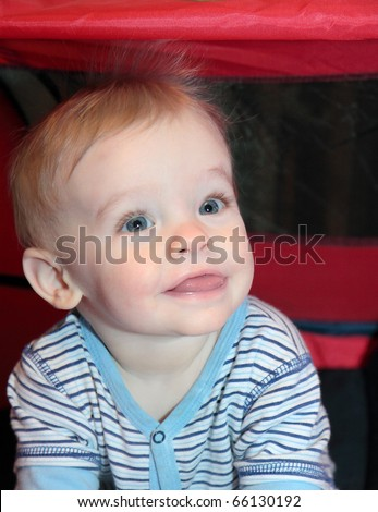 Blonde haired, blue eyed, caucasian baby boy with cute smiling facial expression sits in red tent with static hair standing on end