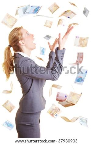 Blonde happy businesswoman catching money raining from the sky