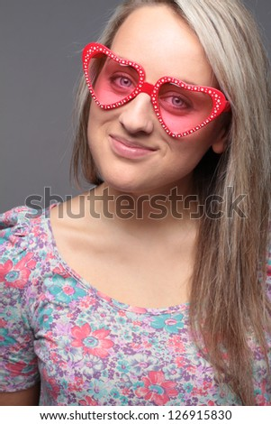 blonde happy teenage girl with heart sunglasses