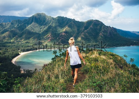 Blonde hiker looks over the ocean on a classic Hawaiian hike. stock photo