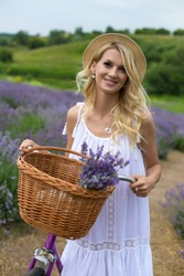 blonde in a white dress and pretty hat smiles right at the camera on a lavender field