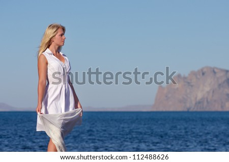 Blonde in a white dress looks at the sea