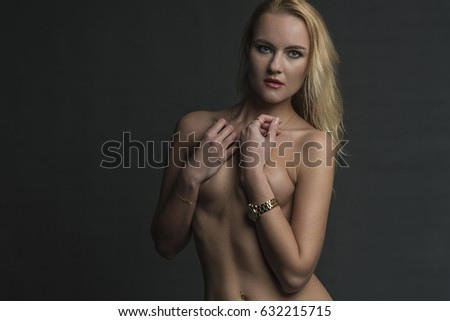 Blonde in blue jeans covers her bare chest with her hands #632215715