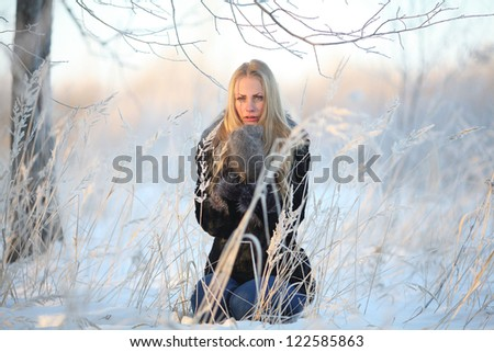 blonde in fur coat in winter forest covered with snow and frost, winter landscape