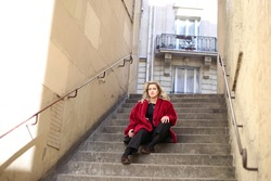 Blonde in pink fur coat sits alone on the stone steps on street in Paris