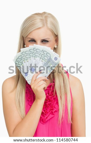 Blonde in pink holding 100 euros banknotes against white background