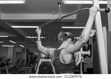 Blonde in the gym. Weight training. Work on the muscles of the back. Dumbbell bench press and pull on poperechchyni. Shaping tell muscles of the back. Women\'s fitness.