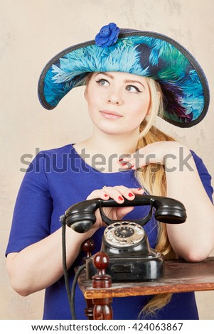 Blonde in wide-brimmed blue ladies hat stands by retro phone at studio.